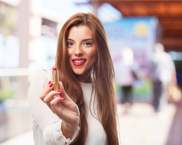 mujer-mujer-sonriendo-mientras-sujeta-pintalabios